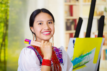 Young brunette woman wearing traditional andean clothing, holding up selection of color pencils and smiling happily, canvas behind, inside studio, garden window background