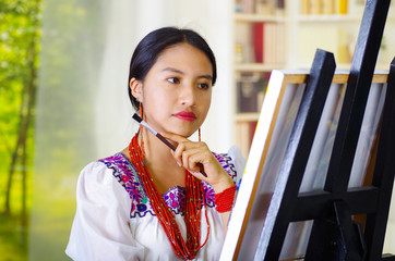 Young brunette woman wearing traditional andean clothing painting on canvas inside studio, evaluating work thoughtful, garden window background