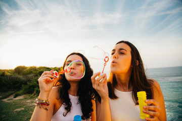 Girls blowing bubbles over the sea