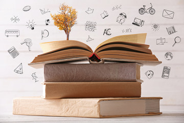 Stack of books with tree, closeup. Icons on blurred white background.