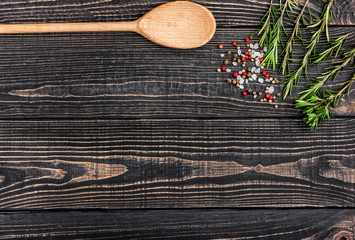 fresh rosemary, salt, pepper and a spoon on a black wooden backg