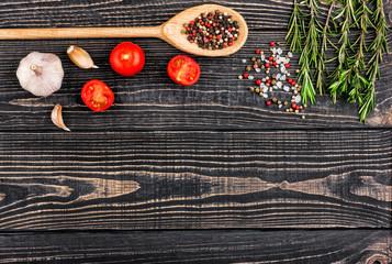 fresh rosemary, salt, pepper, garlic and a spoon on a black wood