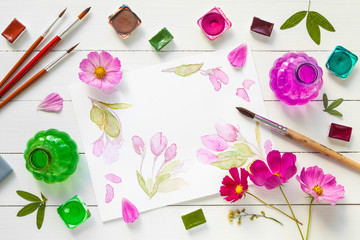 Watercolor paints, brushes for painting, pink flowers and waterc