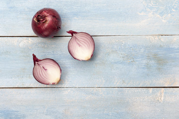 Fresh red onions on a blue wooden background, top view