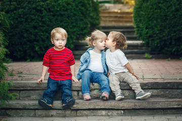 Group of three cute funny adorable white Caucasian children toddlers boys girl sitting together kissing each other, love friendship childhood concept, best friends forever