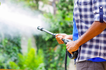 Closeup arms of man wearing square pattern blue and white shirt holding high pressure water gun, pointing towards green garden
