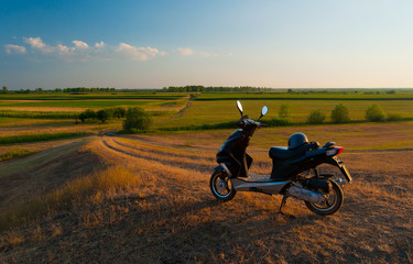 Countryside landscape showing scooter and roads through agricultural fields on sunny day
