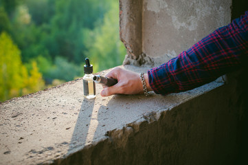 man in a plaid shirt and jeans runs vape juice electronic cigarette. He holds a mechanical mod with RDA. wrists watch and bracelet. against the background of a brick wall