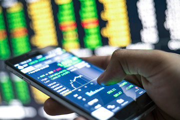 A businessman using a mobile phone to check stock market data.