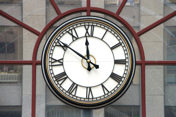 Clock with roman numerals for hours, hands at nine minutes to twelve o'clock on a glass wall, building in background