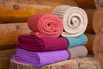 Six roll knitted scarf on wooden background