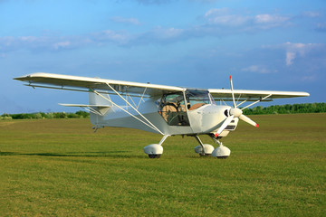 Ultralight aircraft on airport grass in sunset