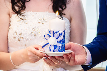 Candle in the hands of the newlyweds.