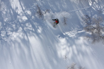 Snowboarder Carves a Slash While He Rides Down the Snowy Mountain Terrain at the Ski Resort at Nevados De Chilean, Chile in the Andes Mountains
