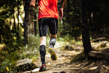 Fotomurales - marathon runner running on stones in forest, on feet compression socks. closeup of trainers