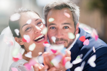 Portrait of happy newlyweds blowing confetti to camera