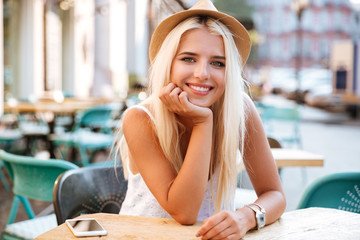 Cheerful woman in hat sitting in outdoor cafe