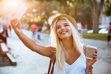 Young smiling girl making selfie while standing on the street