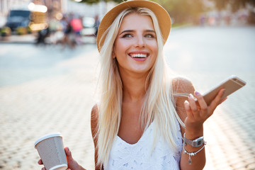 Portrait of a girl in hat holding cup and smartphone
