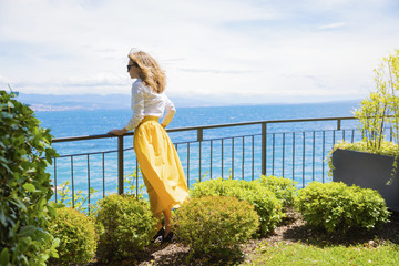 Enjoy sunshine and summer breeze. Full length portrait of an elegant mature lady standing on the balcony overlooking the sea. Rear view.