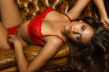 Sexy young woman in red lingerie lying on the sofa.