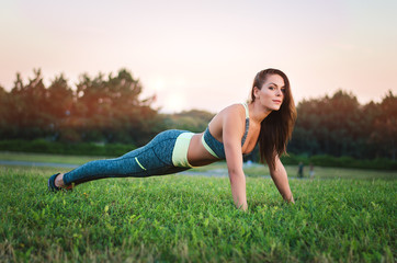 Young attractive woman training in the park. Exercise plank. Fit