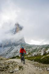View of cyclist riding mountain bike on trail in Dolomites,Tre Cime di Laverado