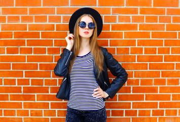 Fashion pretty woman model wearing a black rock style posing ove