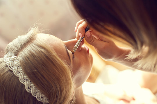 Young beautiful bride applying wedding make-up by make-up artist on the wedding day. Beautiful bride portrait wedding makeup.