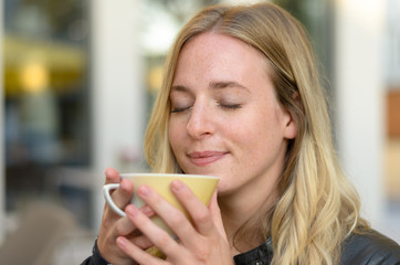 Blissful young woman enjoying coffee