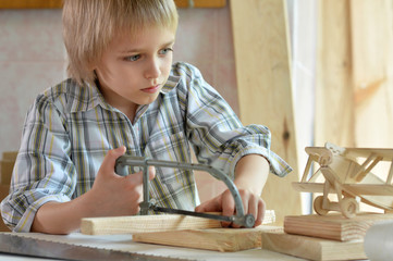 little boy  working with wood