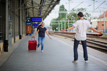 At an empty platform flee a young woman with red suitcase.