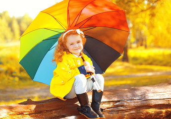 Happy little girl child with colorful umbrella sitting resting o
