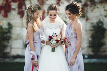 bridesmaids and happy bride admiring bouquet of flowers