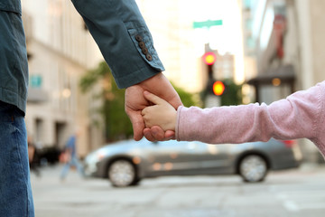 father holding  the daughter/ child  hand  behind  the traffic l