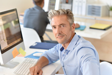 Businessman working in office in front of desktop