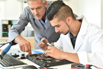 Student in electrical engineering course training with teacher