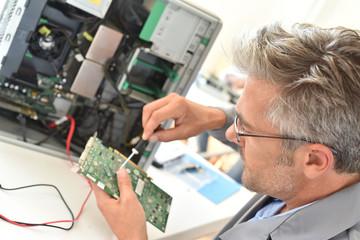 Electrical technician fixing computer hard-drive