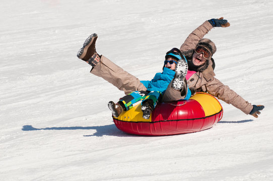 Winter fun. Young woman and little boy sliding downhill on a snow tube