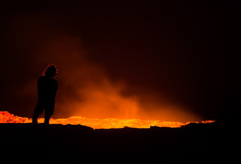 Person standing at the edge of Erta Ale active volcano at night