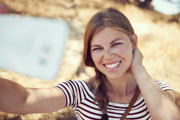 Pretty smiling woman taking picture of herself over rural background outdoors. Concept of summer holidays and travel.