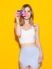 Fashionable girl posing in colorful top and skirt with a vintage camera in her hand a yellow background in the studio. Takes a picture. Sexy Glamour Girl on Yellow background. Concept