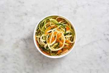 Carrot and zucchini noodles on white marble