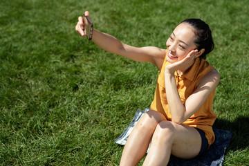 Asian woman in a city park talking selfie photo