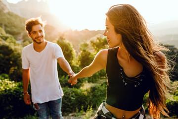 Beautiful young couple enjoying nature at mountain peak.