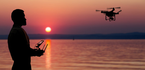 Man flying a drone near seaside at the sunset. Wall mural