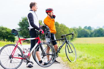 Two sport cyclists having break