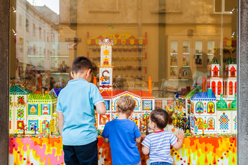 Conceptual photography of children outside the shop with sweets. Storefront caramel products. Candy shop.