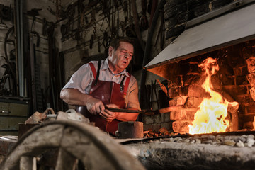 Blacksmith standing on fire in furnace of workshop