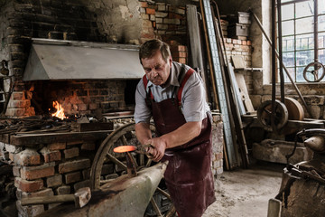 Blacksmith working on hook using hammer and thorn